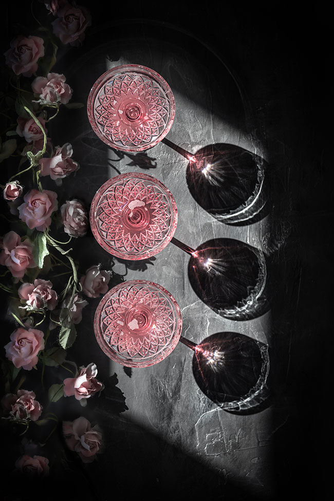 overhead photo of three glasses of rosé colored liquid and roses