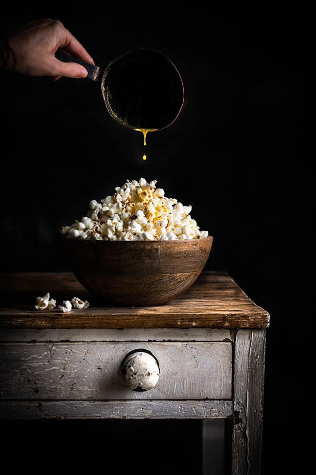photo of a bowl of popcorn with a hand dripping warm butter over the popcorn