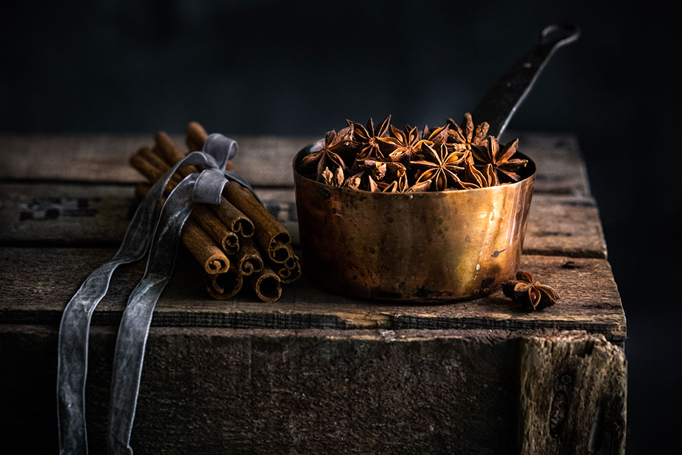 photo of a bowl of star anise spice and cinnamon sticks tied with a ribbon