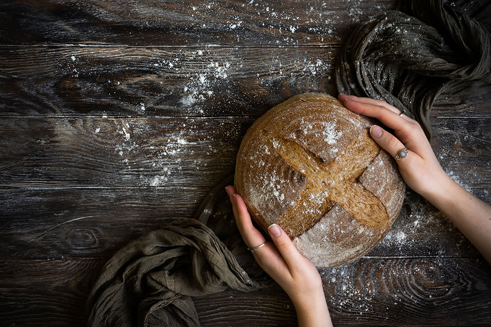 Donna Crous photo of a sourdough bread on a dark wood table with hands holding the bread