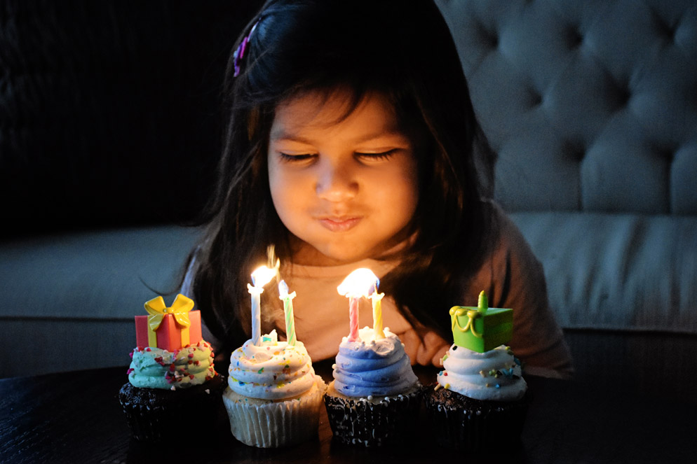 Tamara Lackey photo of a little girl blowing out candles on cupcakes