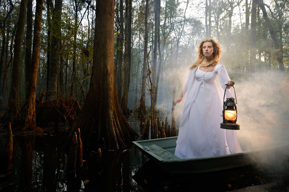 Joe McNally photo of a model on a small boat in a swamp